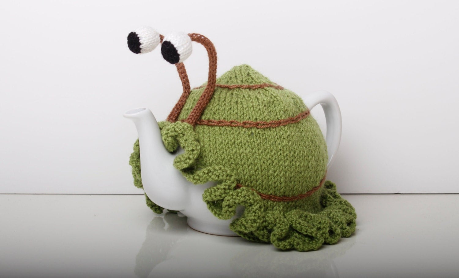 Knitted green snail tea cosy with frilly bottom. Washable fits