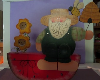 Hand Painted  wooden Country Farmer sitting on a watermelon