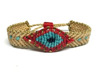 Beige band bracelet with red evil eye
