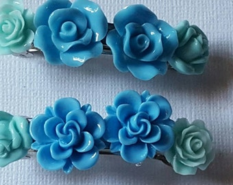 2 inch barrette with 4 resin flowers, 2 teal hugging 2 sky blue flowers, glued across the length of the barrette. Buy 1 or a set of 2!