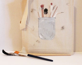 Artist Tote - A natural canvas tote with a blue-gray jar of various paint brushes. Acrylic