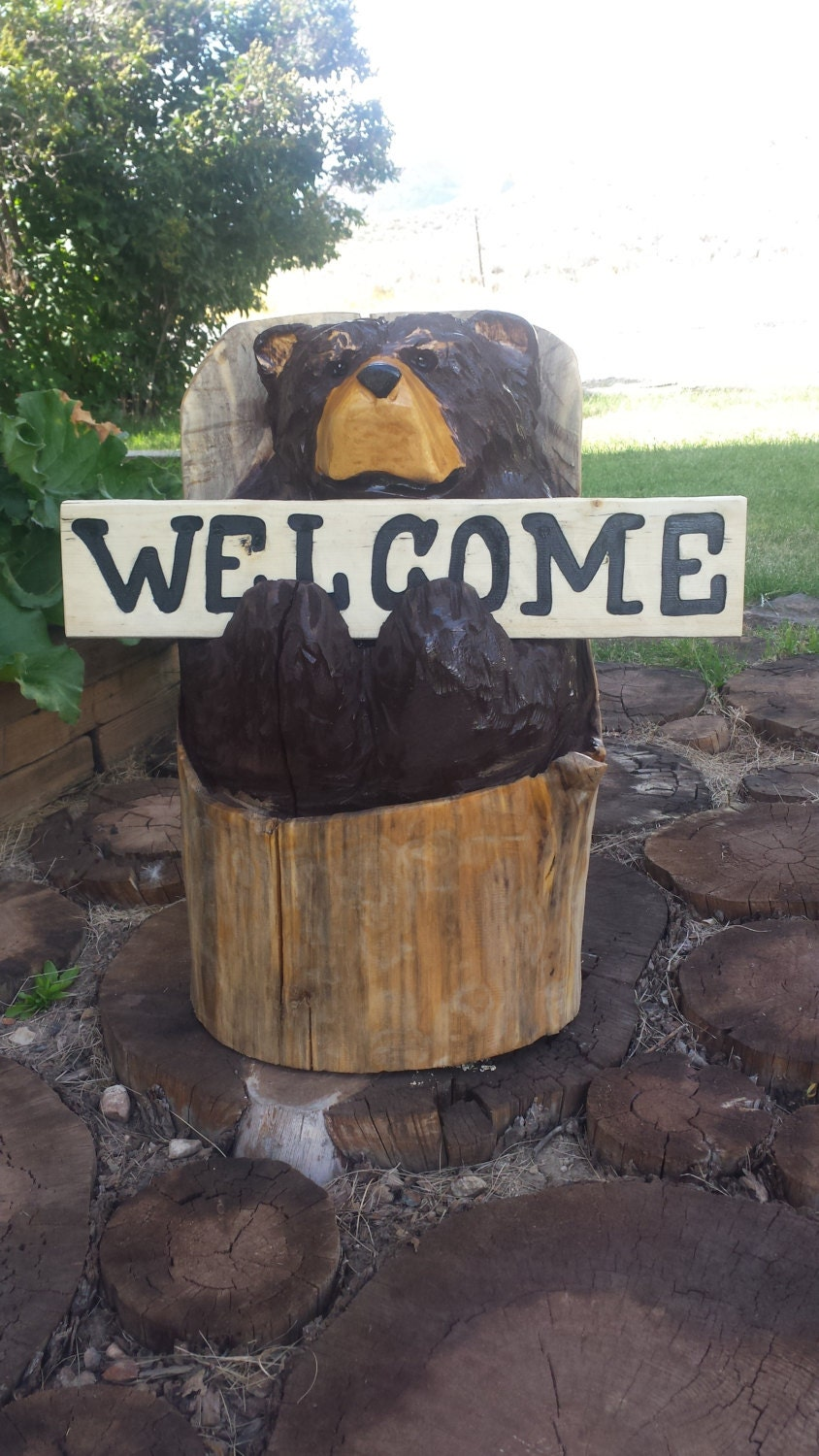 Chainsaw carving carved bear holding welcome sign
