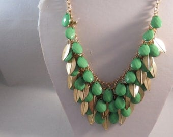 4 Row Bib Necklace with Green Teardrop Beads, Gold Tone Leeves ans Clear Crystal Beads on a Gold Tone Chain