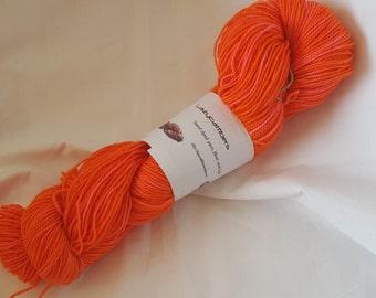 Neon orange with pink hand dyed superwash sock yarn about 450yards