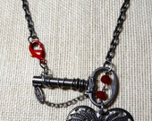 10% off Goth - Vintage silver Paris key, wrapped silver wire, red faceted glass beads, heart dangling below necklace