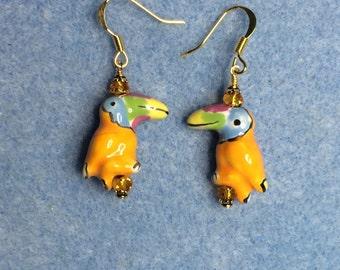 Tangerine orange ceramic toucan bead earrings adorned with tangerine crystal beads.