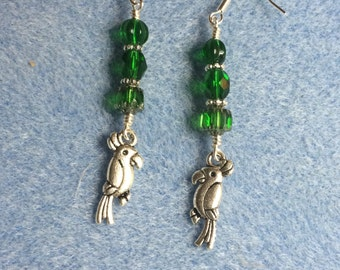 Silver parrot charm dangle earrings adorned with emerald green Czech glass beads.