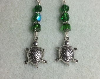 Silver turtle charm dangle earrings adorned with Emerald green Czech glass beads.