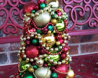 "Christmas Tree made from shatterproof ornaments.  This 16"" X 9"" tree is made in classy colors - golds, reds, dark and light greens"