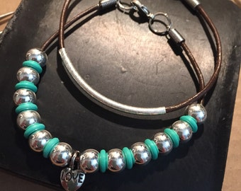 Handcrafted set of two leather bracelets made with silver tone beads and turquoise spacers.