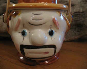 Small canister has Bisque clown sad kind basket.
