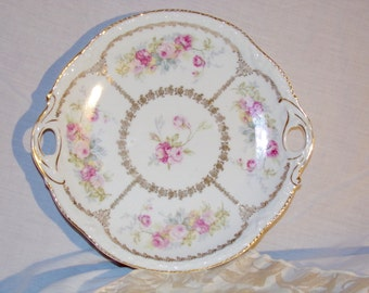 Serving dish with a pink rose pattern and gold leaf accents