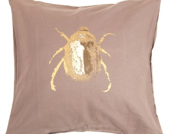 Gold beetle cushion cover.