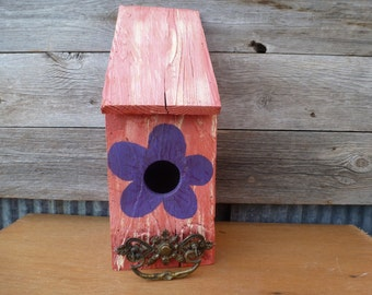 pink birdhouse with purple flower