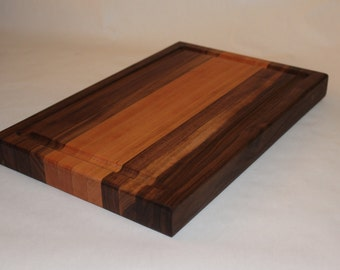 Handcrafted walnut and cherry edge-grain cutting board with juice groove