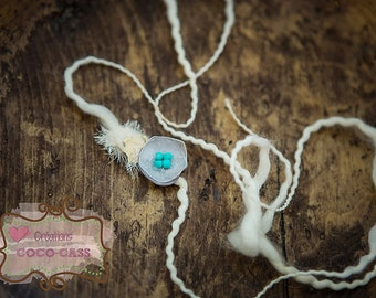 A cream headband with grey flower and turquoise beads