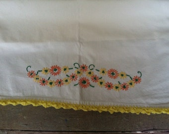 vintage pillowcase embroidered with yellow and orange flowers and yellow crocheted edging