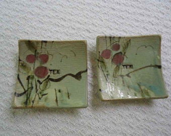 2 tea bag holders by Rich Agness. Glazed in a soft Green, Burgundy,  and black.