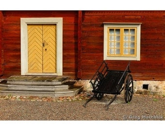 Fine Art Color Photography of Rustic Black Cart in Front of a Home in Sweden