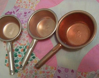 three copper aluminum measuring cups