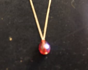 Gold Chain with Red pendant.