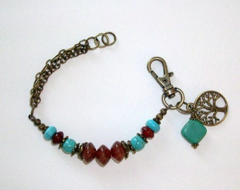 Turquoise and carnelian bracelet with antiqued bronze charm, chain, hand wrapped turquoise bead and a big lobster claw clasp.