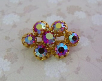 A super retro 1960's / 70's oval dress or collar vintage jewelry brooch in a goldtone metal with sparkly rainbow red aurora borealis stones