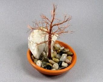 A zen garden in a terra-cotta plate - copper, quartz and river rock combine for a natural, peaceful feeling.