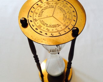 Classic brass hourglass with white sand and demarcated watch shifts