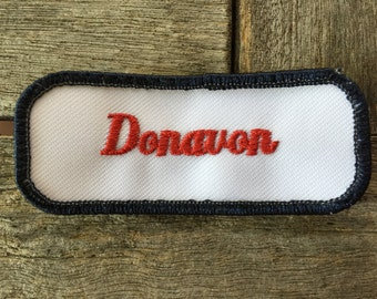 "Donavon - LAST ONE! A white work shirt name patch that says ""Donavon"" in red script with blue border"