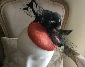 Gorgeous orange round fascinator with black loops, feathers and netting. Stunning!