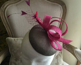 Gorgeous grey round fascinator with magenta loops, feathers and netting. Stunning!