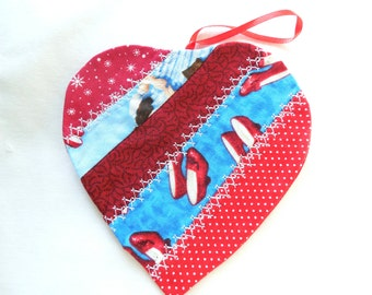 Christmas ornament, heart shaped, has Dorothy's red shoes from Wizard of Oz, 4 1/2 inches by 4 1/2 inche, decorative top stiching.