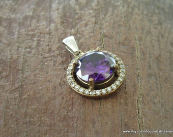 Silver pendant circular shape decorated with shiny beautiful crystals and big lilac crystal in the middle.