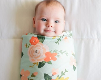 Organic cotton swaddle blanket in mint with coral, peach and blush flowers