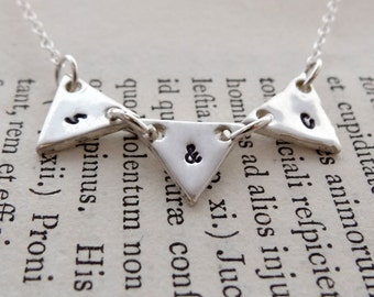 Handmade recycled fine silver hand stamped bunting initial necklace.