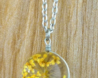 Yellow blossom pendant on silver necklace