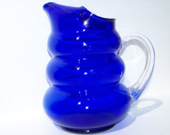 Large cobalt blue pitcher with hand blown clear glass grip.