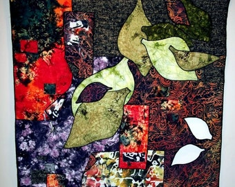 """Art quilt, abstract design of appliqued fabrics, beads, and leaf cut-outs; 30""""x30"""", hung from bamboo dowel"""