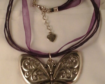 butterfly silver effect alloy pendant on a purple necklace