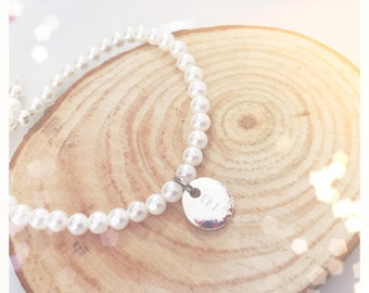 Bracelets with pearls and initials engraved on silver platter