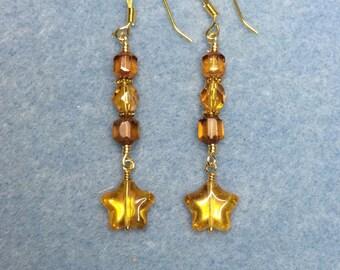 Gold topaz Czech glass star dangle earrings adorned with topaz Czech glass beads.