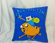 Adventure Time T-shirt repurposed into a decorative pillow cover. Bright blue bedding made from Adventure Time tshirt with Jake & Finn.