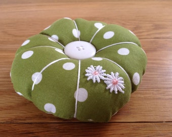 Pin cushion in olive green polka dot cotton fabric with a daisy appliqué and buttons. A fab addition to your sewing box