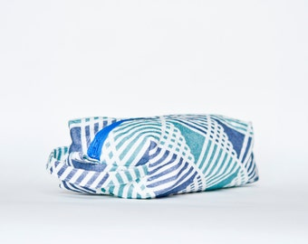 BRAID: Geometric stripe/triangle pattern printed linen toiletry bag with zip. Turquoise, blue.