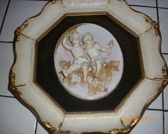 Porcelain Cherub in Gesso Frame