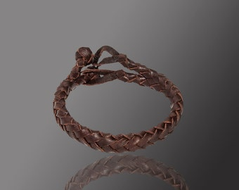 braided leather bracelet with two heads on spike. Dark