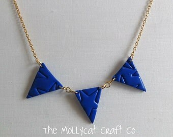 Royal Blue bunting necklace with star pattern imprint.
