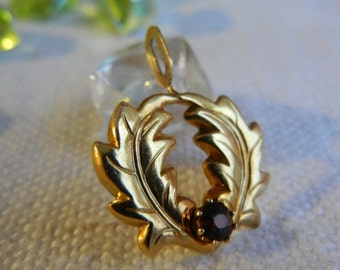 Pendant adorned with gold metal with a Ruby ground oak leaves