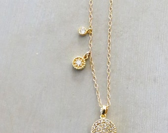 Gold necklace with three cubic zirconia charms hanging from it.  layering necklace, CZ charms, Charm necklace